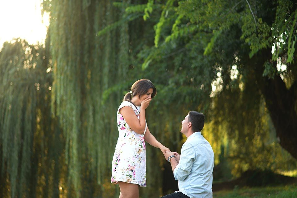man kneeling and proposing to girl